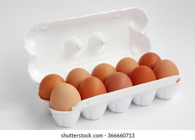 Ten chicken brown eggs in white polyfoam packing on a white background. Not isolate.