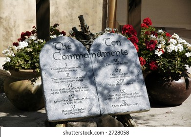 Ten Commandment tablets among pots of flowers.