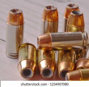Ten different 40 caliber hollow point bullets together on a white wooden background. The bullets have silver cases on several and brass on the others