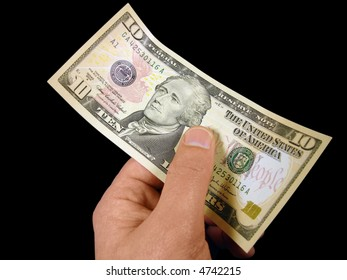 Ten dollar bill in hand against black. Includes clipping path.