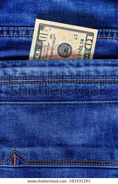 Ten dollar bill in the pocket of  blue jeans. Cash money.