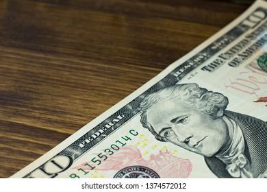 Ten dollars bill fragment of U.S money on wooden background. Macro photo.