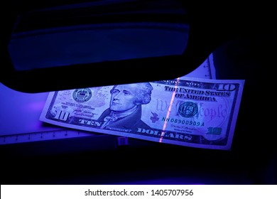 ten dollars on the photo. US banknotes. Equipment for in-depth inspection of money. Checking bills in ultraviolet light. Fake money or financial crisis concept