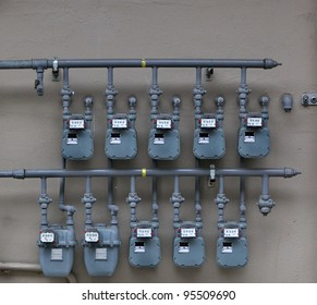 Ten Gray Gas Meters on the wall of an apartment building