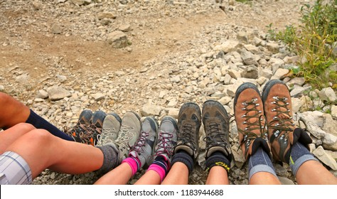 ten hiking boots of a family of five persons in mountain