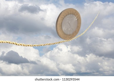 Ten Indian Rupees Coin balancing on golden rope in the sky.