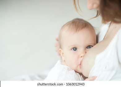 Ten month baby eating mother's milk. Mother breastfeeding baby. Young woman nursing and feeding baby. Concept of lactation infant.