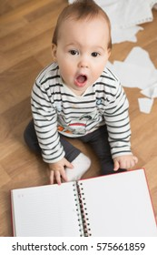 Ten months old baby girl playing with papers and paper folder on the floor; tearing the paper and creating a mess in the room