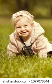 Ten months old girl baby posing in sunny summer park for portrait photo