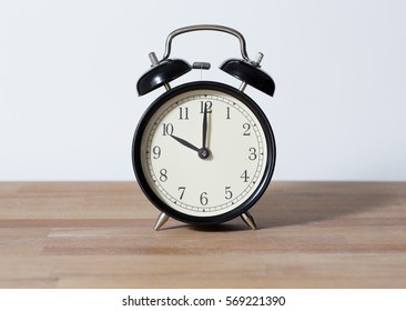 It is ten o'clock. The time is 10:00 am or pm. A retro clock isolated on wooden table. White background. Copy space and cut.
