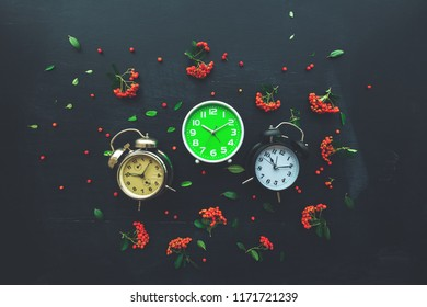 Ten past ten on three different alarm clock, flat lay top view minimal composition of timepieces placed on dark wooden background with decorative wild berry fruit arrangement