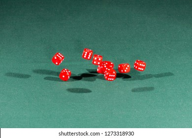 Ten red dices falling on a isolated green table