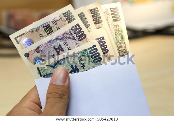 白い封筒に1万5000円の日本のお金を、ビジネスマンは限定フォーカスとソフトフォーカスの封筒に日本の円札を手渡す。ぼかし