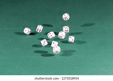 Ten white dices falling on a isolated green table