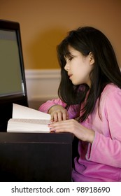 Ten year old biracial Asian girl sitting at computer desk, reading or studying