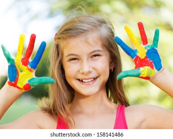 Ten year old girl with hands painted in colorful paints ready for hand prints