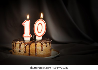 Ten years anniversary. Birthday chocolate cake with white burning candles in the form of number Ten. Dark background with black cloth