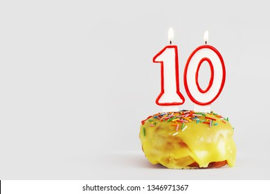 Ten  years anniversary. Birthday cupcake with white burning candles with red border in the form of number Ten. Light gray background with copy space