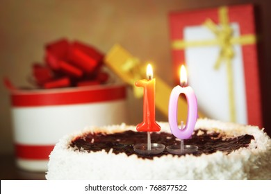 Ten years birthday. Cake with burning candles and gifts