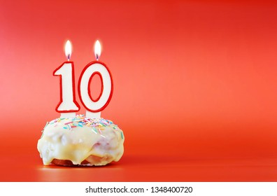 Ten years birthday. Cupcake with white burning candle in the form of number 10. Vivid red background with copy space