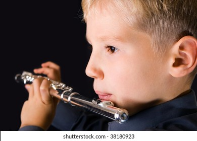 The ten years' boy playing a flute