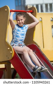 Ten years old girl have fun on children playground while sitting on sliding board