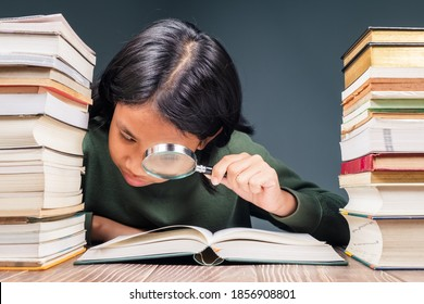 Ten years old girl looking through the magnifying glass on the opened book on the table with a lot of books on pile