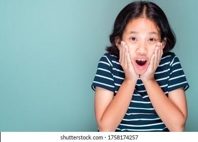 Une fille de 10 ans touche son visage avec un excité astiné ou agréable, enfant thaïlandais en studio photo sur fond vert