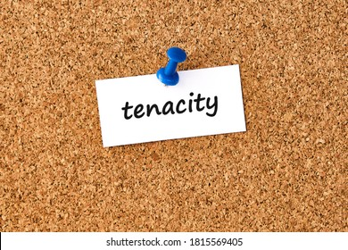 Tenacity. Word written on a piece of paper or note, cork board background.