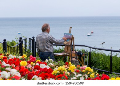 Tenby, Pembrokeshire, Wales - 17 August 2019: Close up of Flowers with Male Artist Painting Coastal Scene of Tenby in the Background