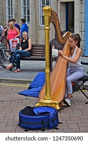 Tenby, Pembrokeshire / Wales UK - 8/3/2018 : A pretty young girl busking by playing a golden Welsh Harp in the centre of this traditional seaside town.