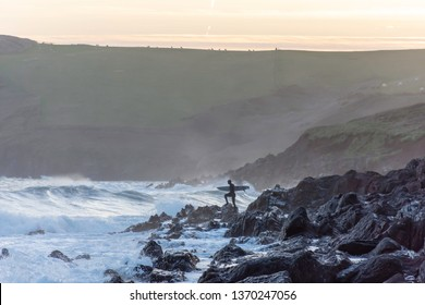 Tenby, Pembrokeshire/UK-04.18.2018:Brave surfer standing on rocky shore, holding surfing board attempting evening surf in rough sea at dusk.Healthy lifestyle, extreme sport.Recreational pursuit.