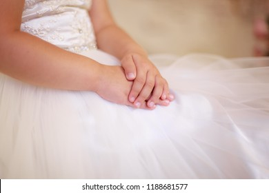 tender baby hands, girl in dress, tulle, closeup