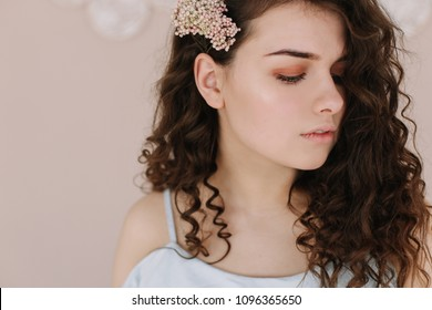 Tender beautiful girl with curls and flower in hair on a pink background. Summer beauty. Romantic shot