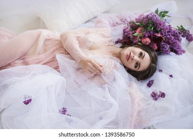 Tender beautiful girl lays on the silk and lace linens with peta