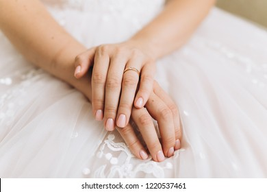 Tender beautiful hands of young lady bride in white fashionable wedding dress with engagement ring