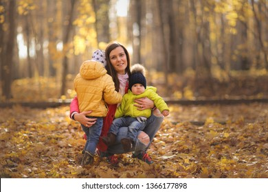 tender beautiful mother brunette with long hair with two sons. Walk in the autumn park