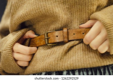 tender and beautiful women's hands touch the leather belt on the waist of a woman dressed in warm sweater and a long skirt. Concept for a women's store or showroom