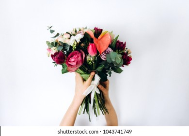 Tender bouquet of different flowers in hands on as background white wall