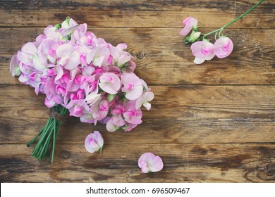 Tender bouquet of sweet peas, on wooden table, vintage style, top view