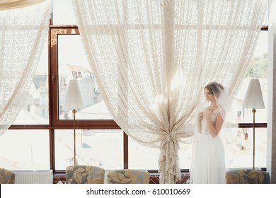 Tender bride covered with a veil stands before windows with lace curtains