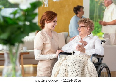 Tender caretaker making an elderly woman ia a wheelchair laugh in a day care facility for people with impairments.