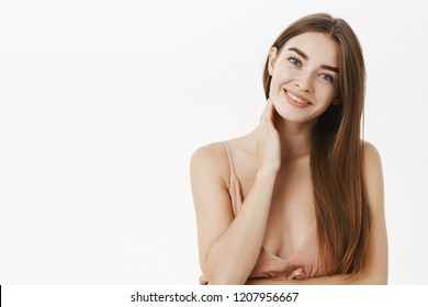 Tender and caring feminine innocent girl with long brown healthy hair tilting head flirty smiling gently and touching neck feeling shy and sensual posing in beige dress over gray background