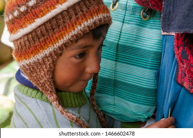 A tender child takes refuge in the skirts of his mother. February 21, 2015, Huancayo Peru