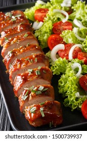 Tender cooked pork tenderloin in honey-garlic sauce served with vegetable salad close-up on a plate on the table. vertical