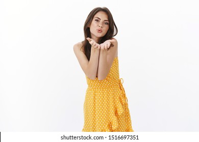 Tender coquettish pretty brunette woman in summer yellow dress, blowing wind kiss, hold palms near pout lips to send muah camera, look flirty and silly stand white background romantic seductive mood