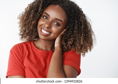Tender friendly-looking attractive young african-american woman with curly afro hairstyle combing hair with hand gently, tilting head and smiling lovely at camera with flirty caring gaze