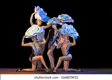 Tender garden. Young female dancers with huge floral hats in neon light on black background. Graceful models, women dancing, posing. Concept of carnival, beauty, motion, blooming, spring fashion.