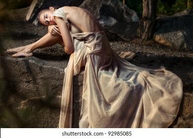 Tender girl is sitting resting her head on the knees