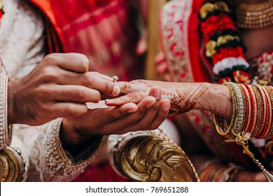 Tender hands of an Indian bride covered with henna tattoo hold groom's hand while he gives her a wedding ring